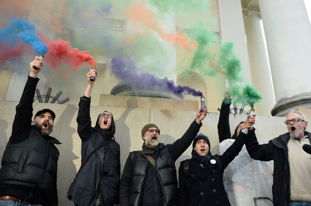 Civic rights activists burn flares in front of City Hall in Warsaw, Poland, on Monday to protest what they saw as authorities' failure to respond properly to the behavior of nationalists during the Independence March on Saturday.