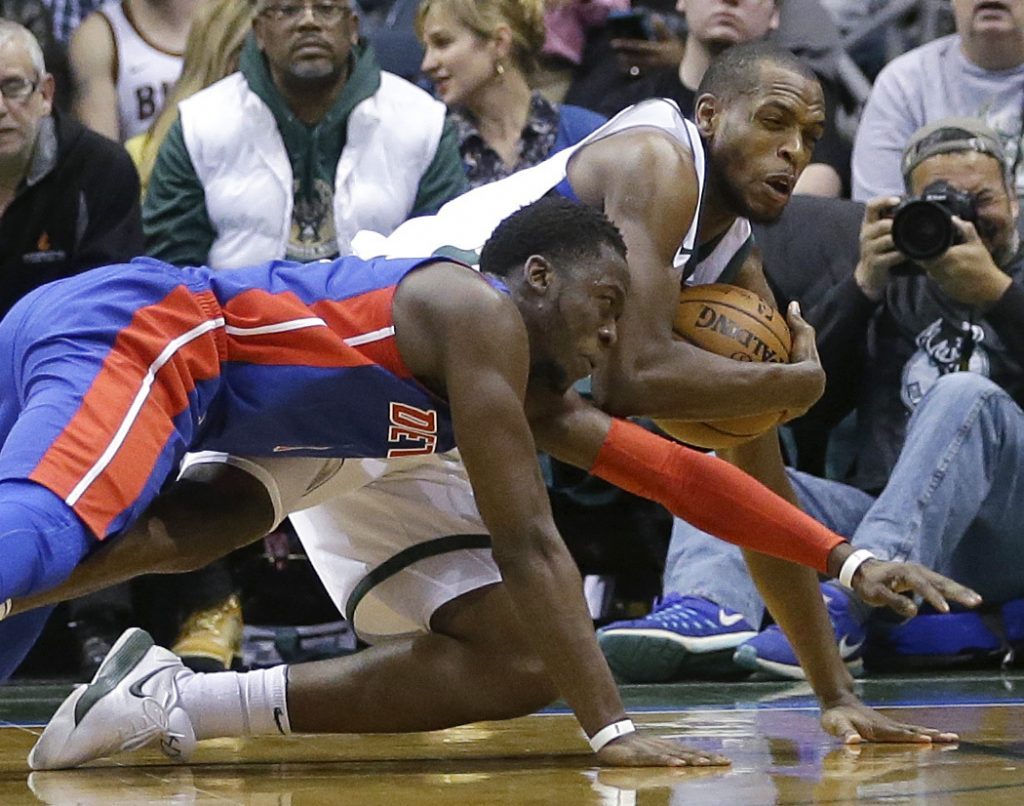 Milwaukee's Khris Middleton, top, vies for a loose ball with Detroit's Reggie Jackson in the second half Wednesday night.