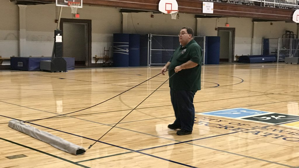 Jim Gauthier pulls a wet-dry mop over the gym floor Wednesday morning at the Lewiston Recreation Center. Employees were cleaning up Wednesday after someone broke in overnight and created a mess.