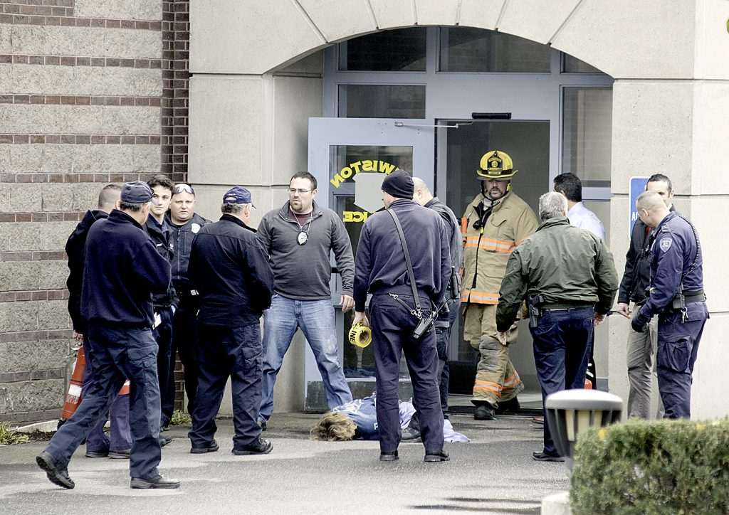A woman lies on the ground as rescue personnel gather outside the Lewiston Police Department after she was removed from the department lobby, where she threatened to set herself afire.