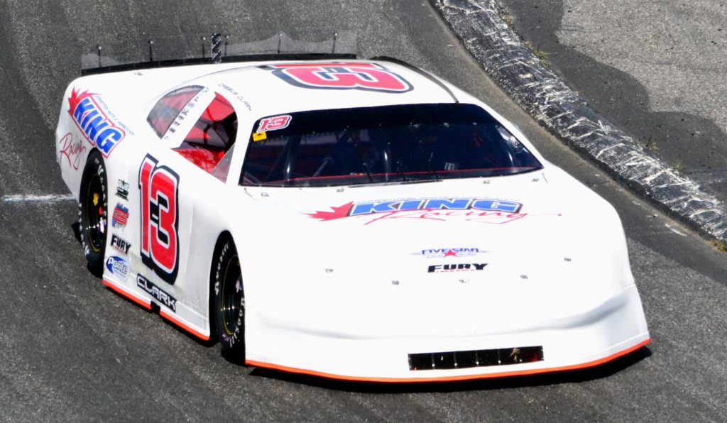 Farmington native Cassius Clark drives off Turn 4 at Oxford Plains Speedway this season. Clark is in North Carolina awaiting the arrival of his King Racing team transporter that has been delayed at the border crossing in Houlton since Tuesday.
