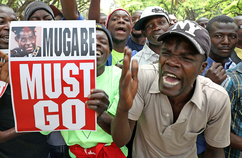 Protesters call for Zimbabwean President Robert Mugabe to resign across the road from parliament in Harare, Zimbabwe, Tuesday.