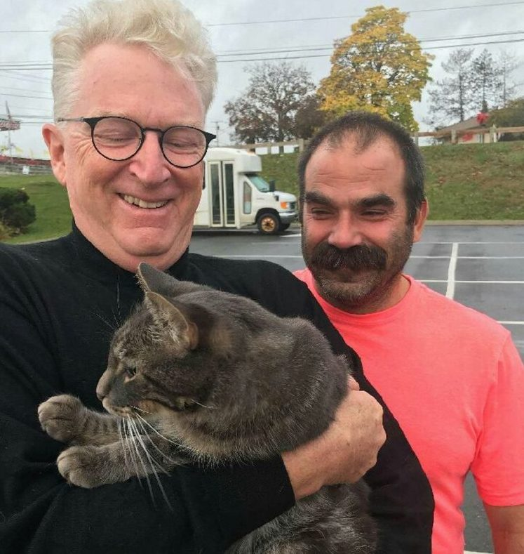 George Lichte of Kennebunkport holds his cat, Romeo, as Kevin Taft of Solon, who found the cat in Unity after it had been missing for a year, watches.