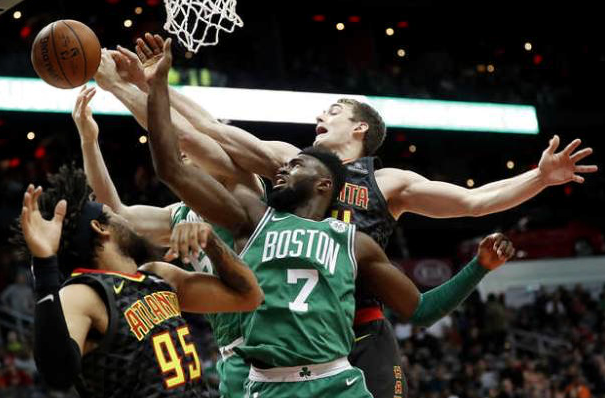 Boston Celtics' Jaylen Brown reaches for a rebound with teammate Aron Baynes, rear, against Hawks' Tyler Cavanaugh, right, and DeAndre' Bembry in the first quarter in Atlanta on Saturday.