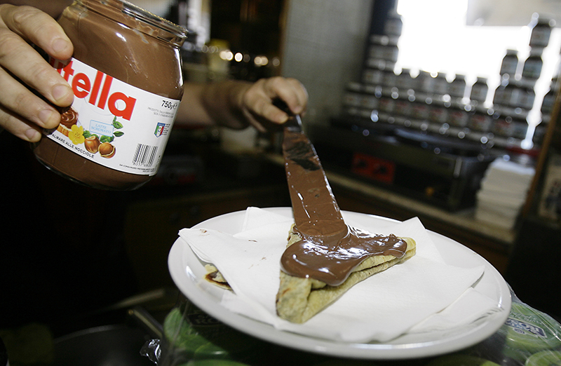 The bartender spreads Nutella on a crepe in a creperie in Rome in 2010.