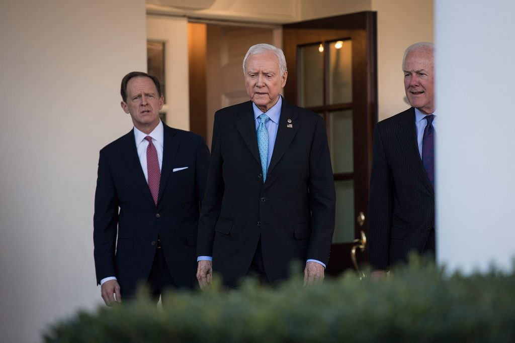 Senate Finance Committee Chairman Orrin Hatch, R-Utah, center, and Sens. John Cornyn, R-Texas, right, and Patrick Toomey, R-Pa., walk from the West Wing to speak to reporters after a meeting with President Trump on Monday.