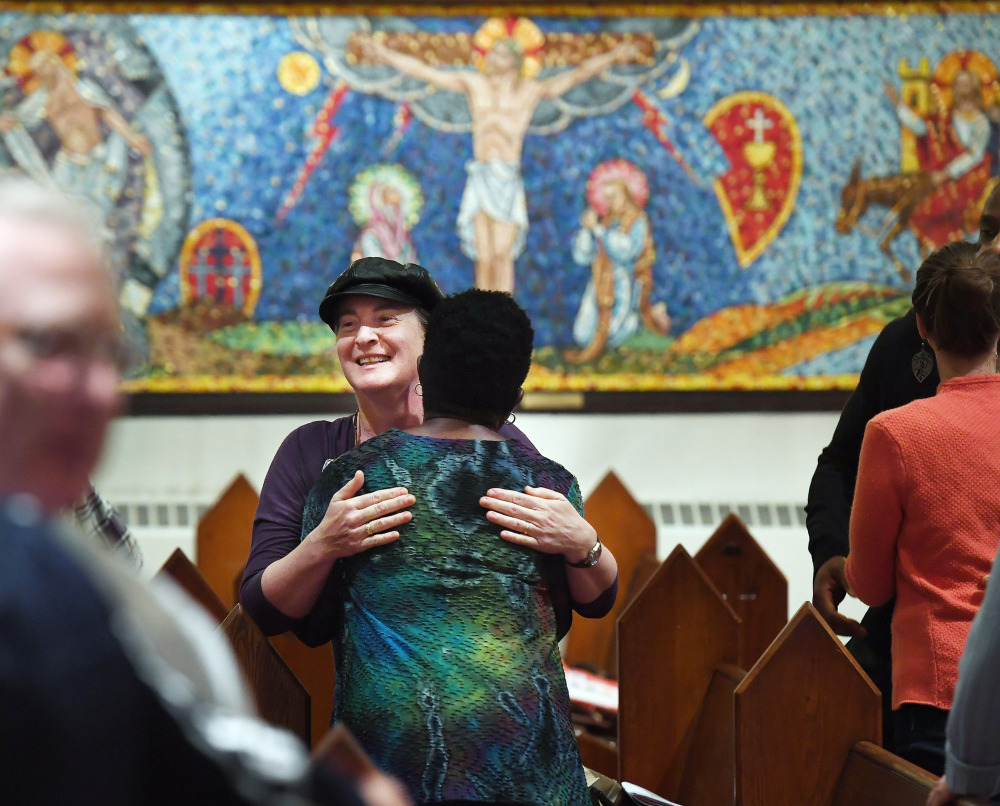 "Isabelle Melese-d'Hospital, facing the camera at center, embraces Charleen Ward during a service at St. Margaret's Episcopal Church in the District of Columbia. ""I needed to come after the (2016) election. ... I needed to have that family support of the church,"" Ward said."