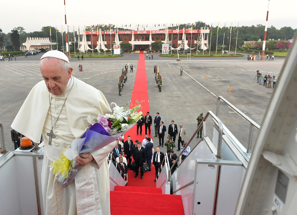 "Pope Francis boards an airplane as he prepares to depart from the airport in Dhaka, Bangladesh, Saturday. Francis urged Bangladeshi priests and nuns to resist the ""terrorism of gossip"" that can tear religious communities apart, delivering one of his spontaneous speeches to the country's Catholic leadership at the close of his Asian tour."