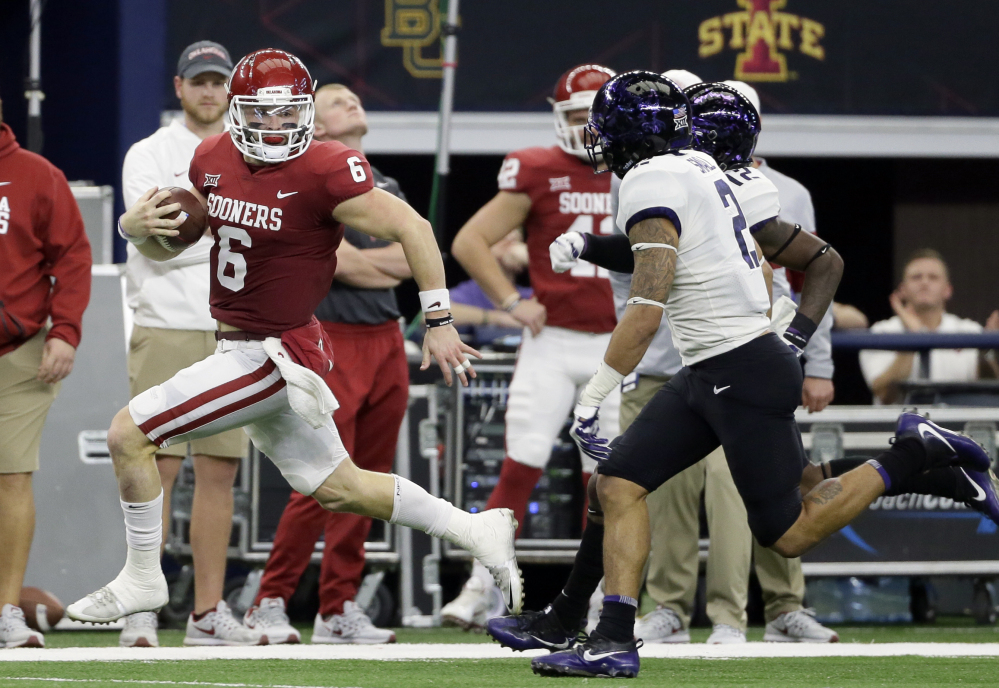 Oklahoma quarterback Baker Mayfield, left, runs for yardage as TCU safety Niko Small gives chase in the first half of the Big 12 Conference championship on Saturday, in Arlington, Texas. The Sooners won, 41-17.