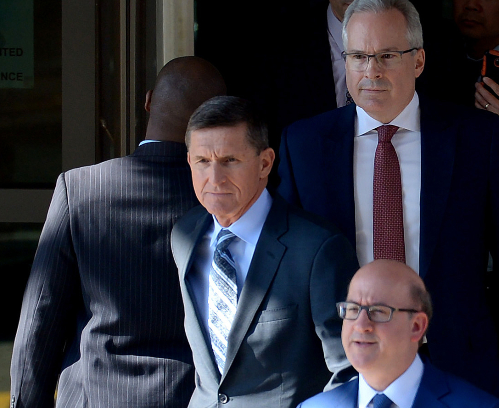 Washington Post/Essdras M Suarez Former National Security Adviser Michael Flynn leaves the E. Barrett Prettyman U.S. Courthouse on Friday surrounded by members of his legal team.