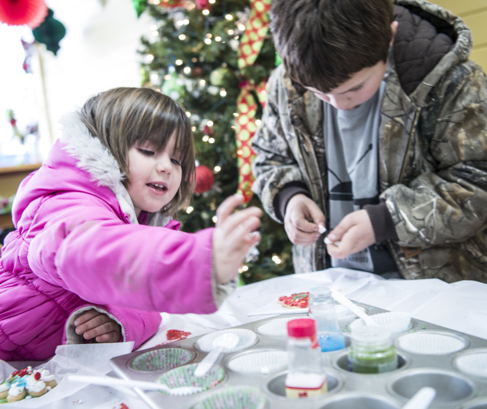 Hannah Veilleux, 4, makes holiday cookies Saturday with her brother, Isaiah Vear, 11, at Holy Cannoli in Waterville. The event was part of the city's Joy to the Ville activities.