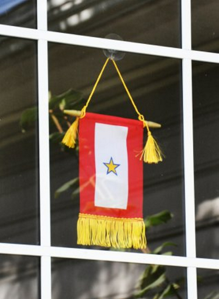 Displaying a Service Flag with a blue star covered by a gold star signifies that a family member died while serving in the armed forces. A Gold Star is only realized through years of absence.