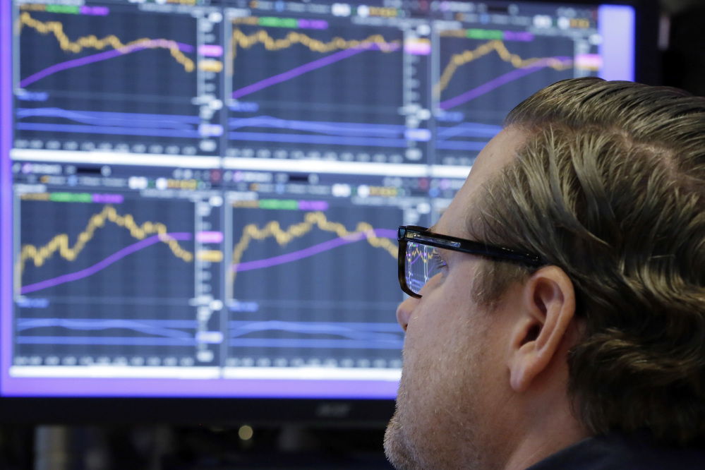 Specialist Gregg Maloney works Monday at his post on the floor of the New York Stock Exchange. The exchange was nearly evenly split between stocks that rose and fell.