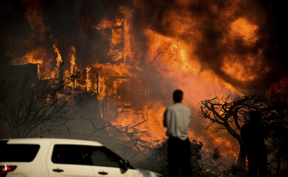Associated Press/Noah Berger A man watches flames consume a home as a wildfire rages in Ventura, Calif., on Tuesday. Ferocious winds in Southern California have whipped up explosive wildfires, burning a psychiatric hospital and scores of other structures.