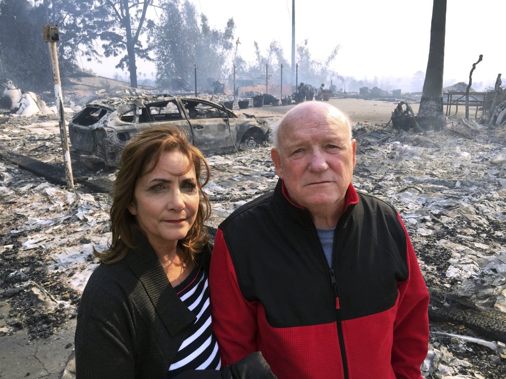 "Linda and John Keasler pose for a photo Tuesday in front of the ruins of their home at the Hawaiian Village Apartments, which was destroyed by fire. ""It is sad,"" said John Keasler, 65."" We loved this place. We lost everything."""