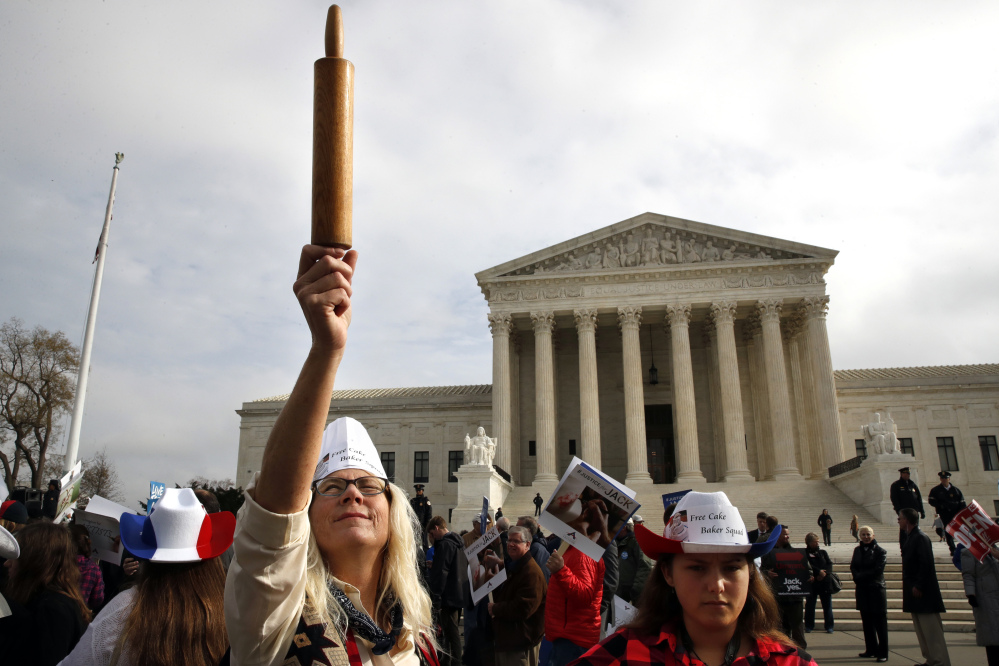 A demonstrator outside the U.S. Supreme Court Tuesday holds up a rolling pin in support of baker Jack Phillips during arguments in the case of Masterpiece Cakeshop vs. Colorado Civil Rights Commission, also known as the wedding cake case.