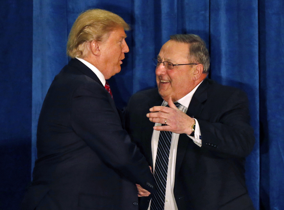 Gov. Paul LePage greets Donald Trump at a March 2016 campaign appearance in Portland. In letting a lawsuit against the president go forward, a federal judge cites LePage's stay at the Trump Organization's hotel when he was on official business with the federal government that included discussions with the president.