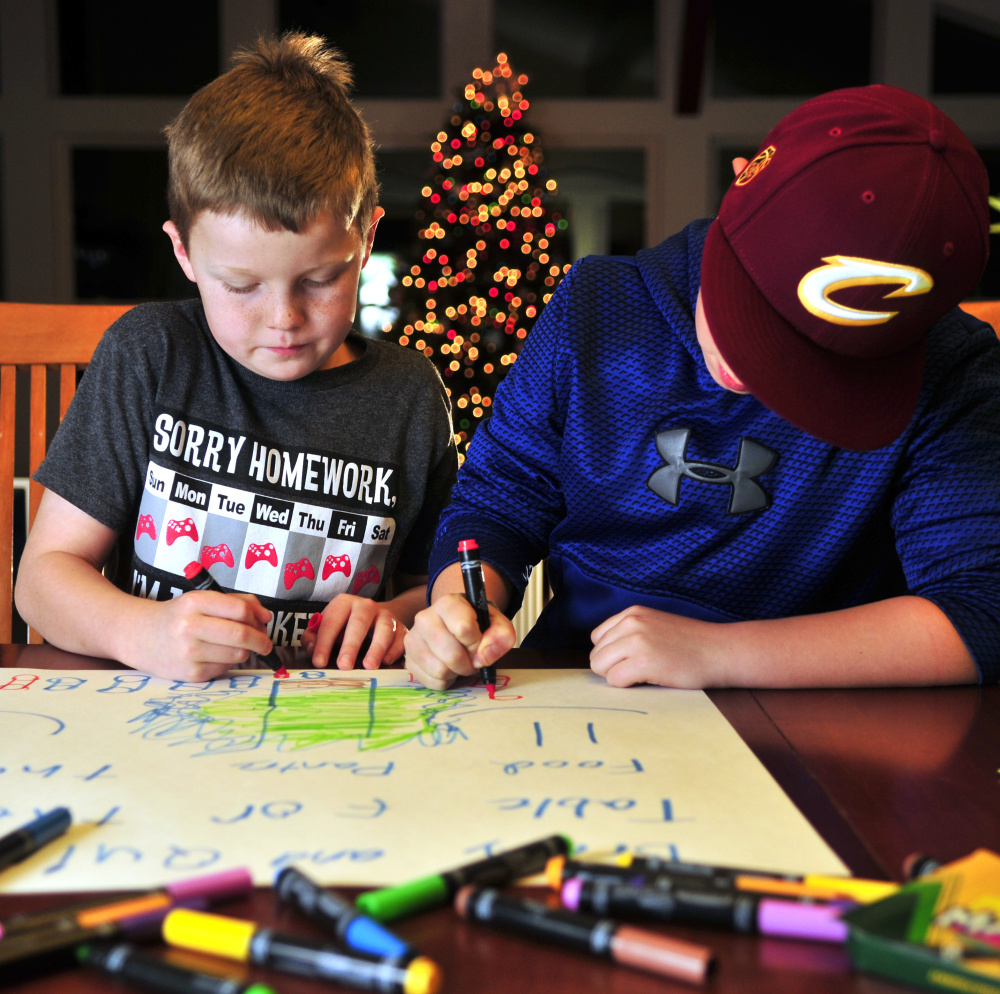 Quincy Emmons, left, and Brady Alexander work on a poster Thursday in Richmond. They plan to staff a table Friday evening at the Richmond tree-lighting to collect nonperishables for the Richmond Food Bank.
