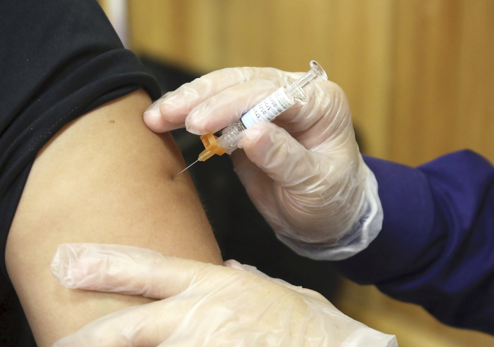 A flu vaccine injection is administered by a pharmacist in Brownsville, Texas. Health officials say the flu vaccine seems well matched to the viruses making people sick this year, but it's too early to tell how bad this season will be.