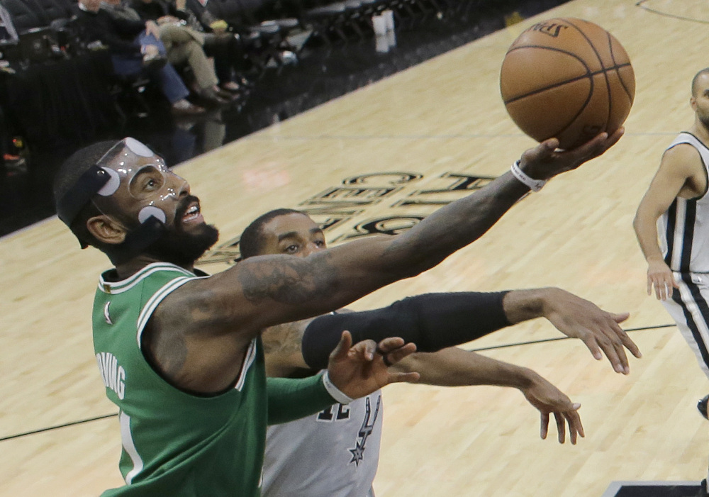 Boston's Kyrie Irving takes a shot while being defended by San Antonio's LaMarcus Aldridge on Friday in San Antonio. Irving had 36 points but missed a 3-pointer at the buzzer and the Celtics lost 105-102.