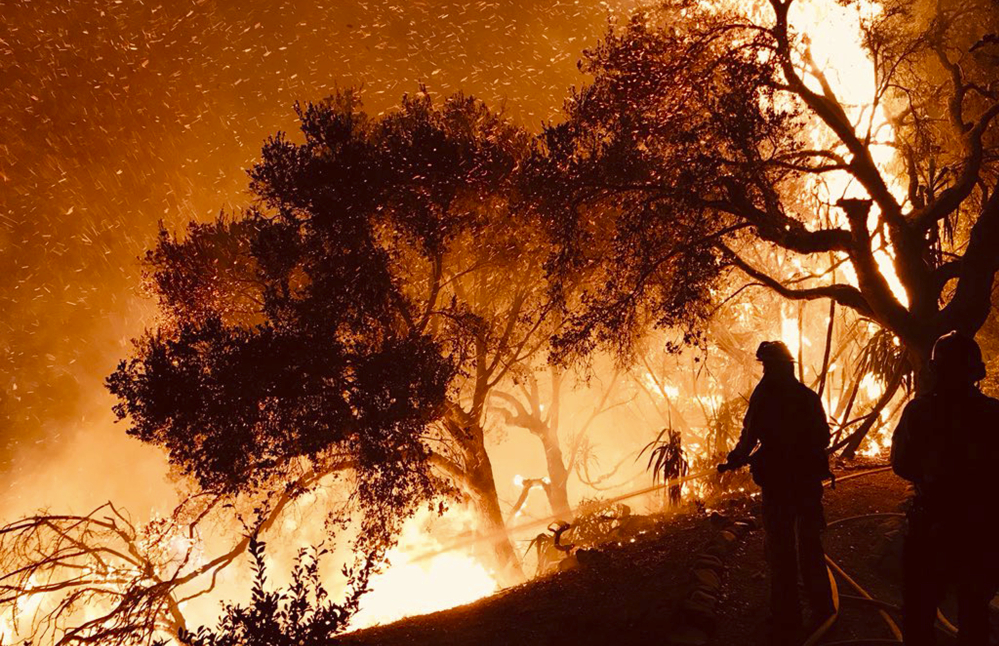Santa Barbara County Fire Department personnel knock down flames as they advance on homes atop Shepherd Mesa Road in Carpinteria, Calif. A flare-up on the western edge of Southern California's largest wildfire sent residents fleeing.