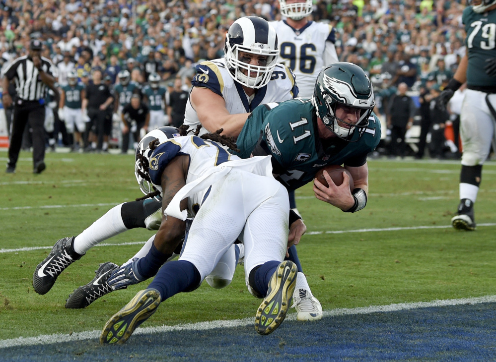 Philadelphia quarterback Carson Wentz is tackled during the second half against the Los Angeles Rams on Sunday. Wentz tore his left ACL and will miss the rest of this season and the playoffs.