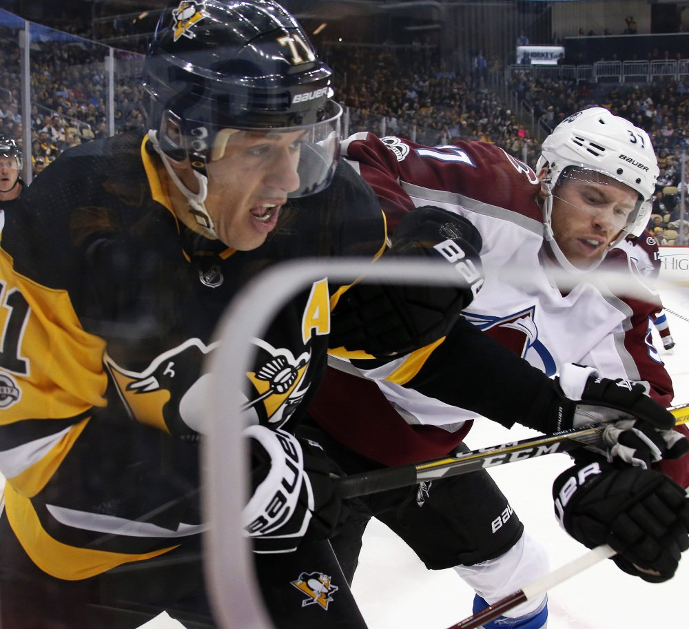 Evgeni Malkin, left, of the Penguins and J.T. Compher of the Avalanche battle for the puck during Colorado's 2-1 victory Monday night in Pittsburgh.