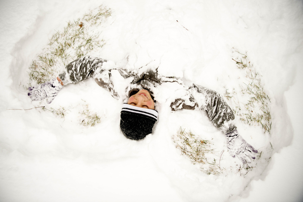 Matt Murphy, 13, makes snow angels in the fresh snow at Veteran's Memorial Park in Waterville after getting out of school early Tuesday.