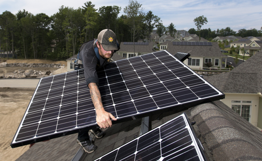 Jack Doherty of ReVision Energy installs a solar panel in Falmouth. Homeowners get a credit for excess energy fed into the grid.