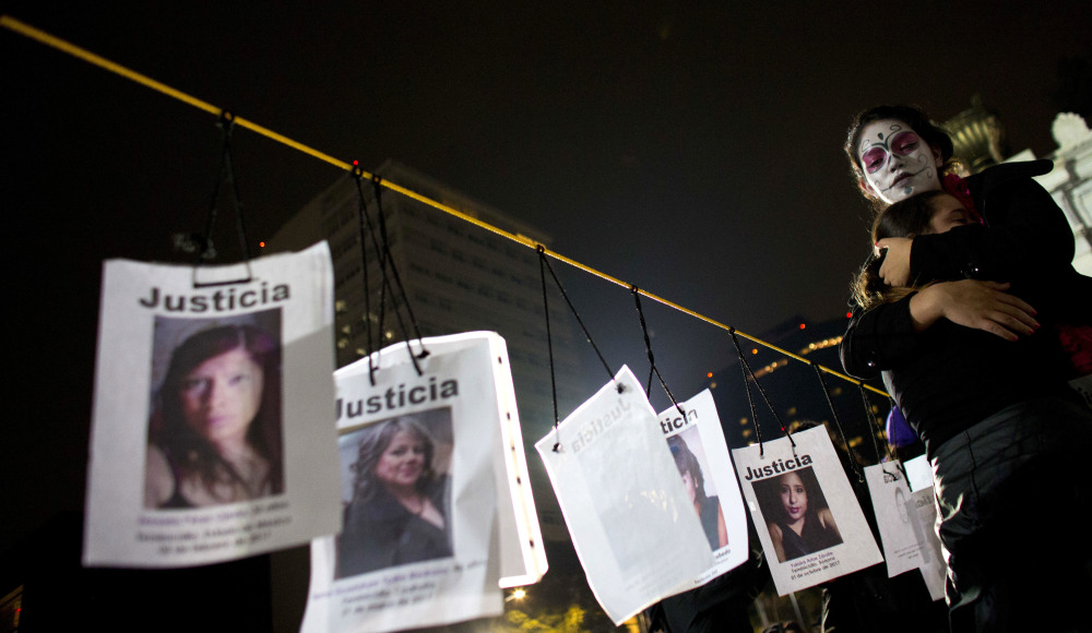 A woman hugs a girl beside images of slain women in Mexico City following a march calling for justice for homicide victims. Of the 52,210 killings of women in Mexico since 1985, nearly a third occurred in the past six years, a report from Mexico's Interior Department said.