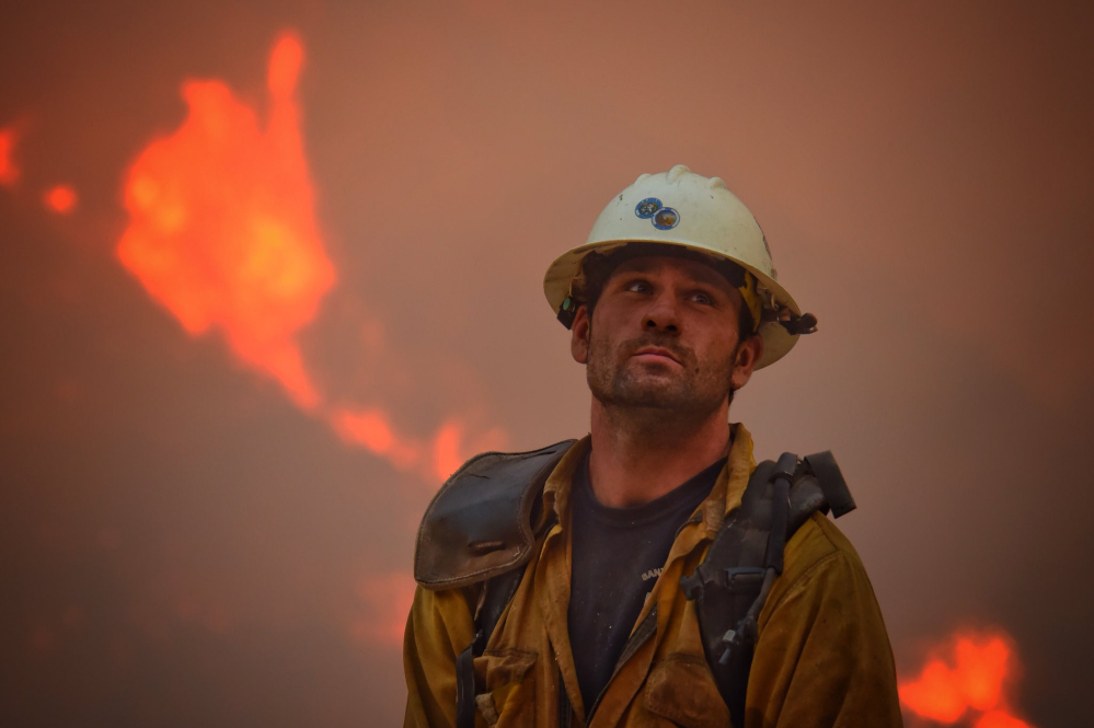 Santa Barbara County Fire Department crew member Nikolas Abele keeps an eye on a hillside for stray embers during an operation in Santa Monica Canyon in Carpinteria, Calif., on Monday. Ash fell like snow and heavy smoke had residents gasping.