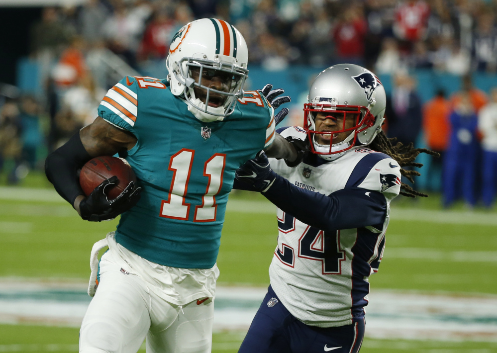 New England Patriots cornerback Stephon Gilmore (24) attempts to tackle Miami Dolphins wide receiver DeVante Parker (11), during the first half of an NFL football game, Monday, Dec. 11, 2017, in Miami Gardens, Fla. ()