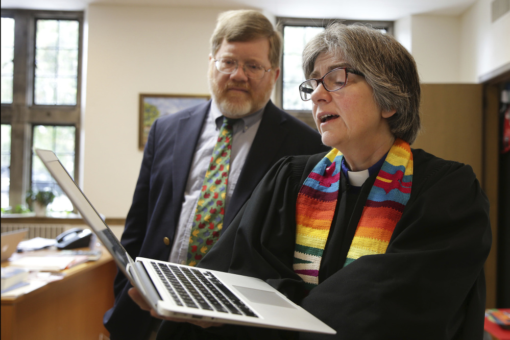 The Rev. Carolyn Winfrey Gillette, co-pastor of Overbrook Presbyterian Church, sings one of her hymns as her husband and co-pastor, the Rev. Bruce Gillette, listens in their office last month at Overbrook Presbyterian Church in Philadelphia.