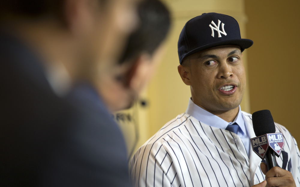 New Yankee Giancarlo Stanton talks with reporters on set during the Major League Baseball winter meetings in Orlando, Fla., Monday, Dec. 11, 2017. (AP Photo/Willie J. Allen Jr.)