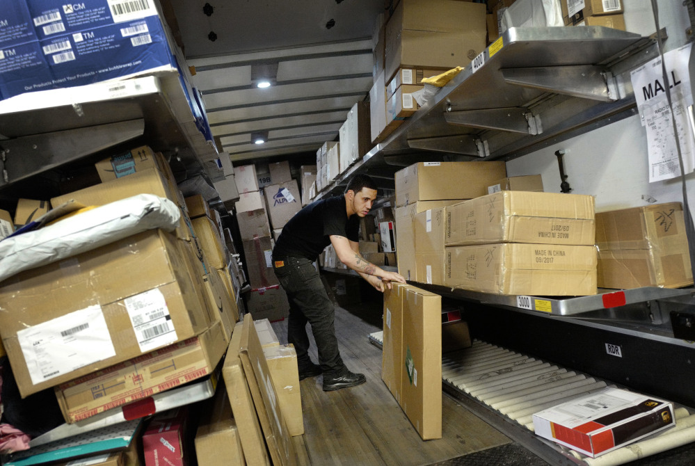 A UPS employee loads packages onto a truck at a company facility in New York in this May file photo. With Christmas on a Monday, most retailers have one less day to get packages delivered on time. UPS said earlier in December that some package deliveries were being delayed because of a surge of orders from online shoppers after Thanksgiving.