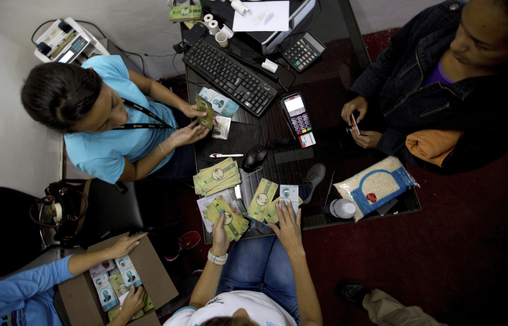 A customer buys bank notes called panales at a communal bank in Caracas, Venezuela, on Friday. Associated Press/Fernando Llano
