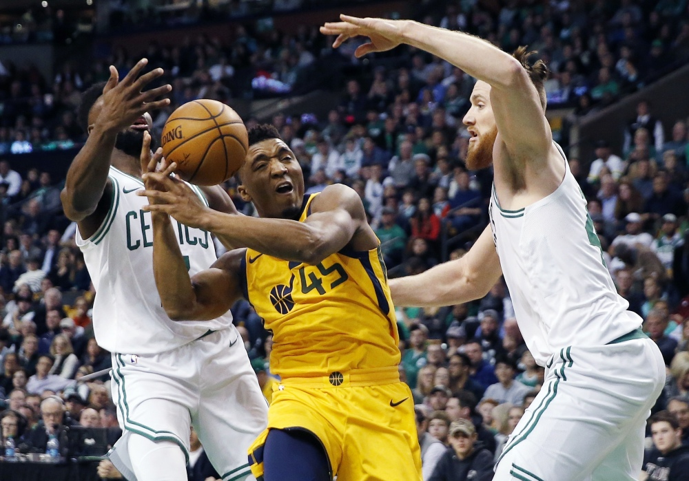 Utah's Donovan Mitchell drives for the basket between Boston's Jaylen Brown, left, and Aron Baynes in the second quarter Friday night in Boston.