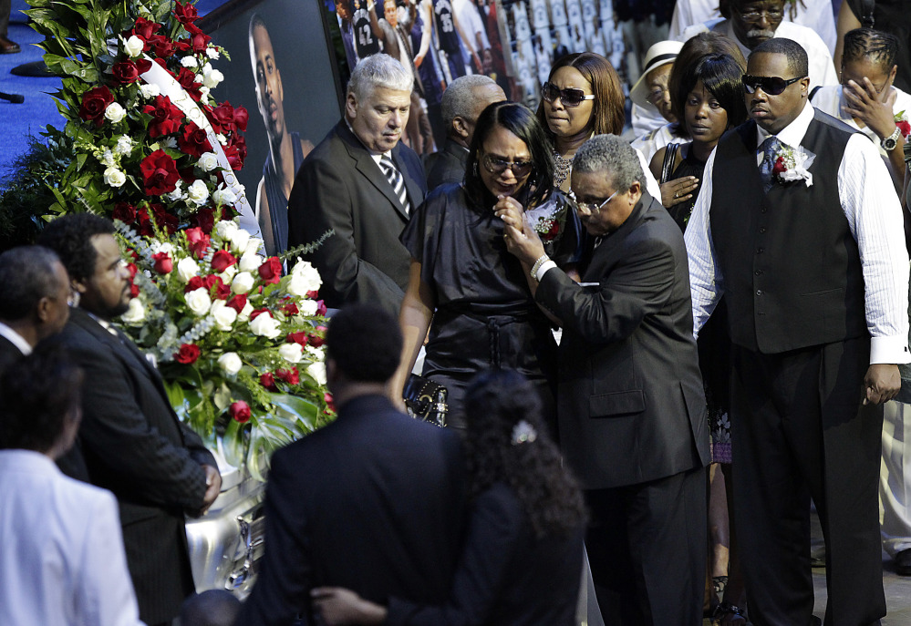 Sherra Wright, the ex-wife of slain NBA basketball player Lorenzen Wright, grieves at his casket during a memorial service at the FedExForum in Memphis, Tenn. Authorities said Saturday that she was charged with first-degree murder in his death.