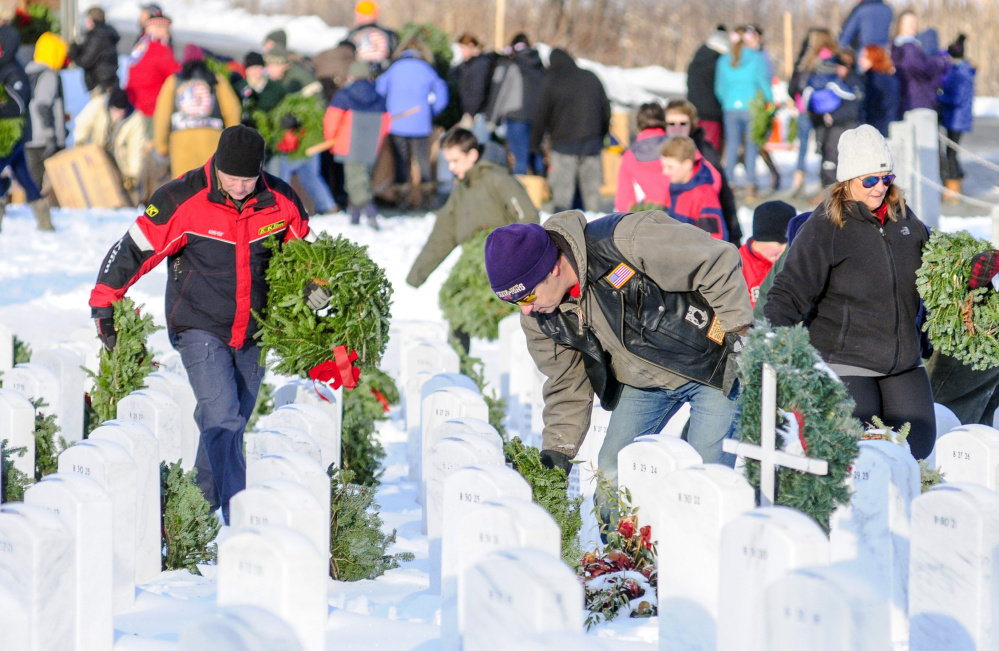Above, volunteers place wreaths on grave markers Saturday at the Maine Veterans Memorial Cemetery on Mount Vernon Road in Augusta.