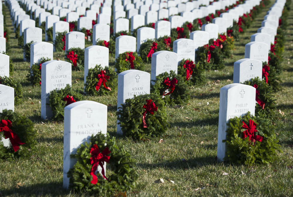 Left, wreaths rest against headstones at Arlington National Cemetery as Wreaths Across America places remembrance wreaths on headstones at the cemetery in Arlington, Va., on Saturday. Associated Press/Cliff Owen
