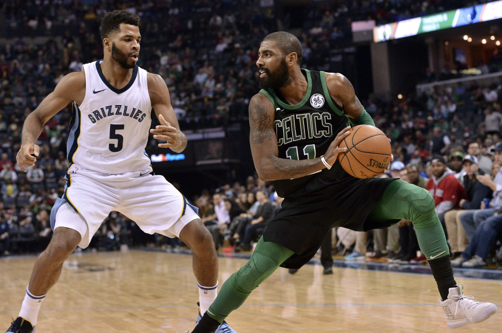 Celtics guard Kyrie Irving controls the ball against Grizzlies guard Andrew Harrison in the second half Saturday night in Memphis, Tenn. Irving scored 20 points and Boston won 102-93.