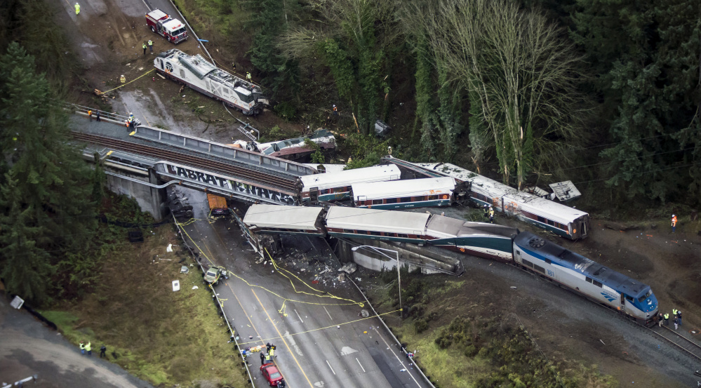 Cars from a derailed Amtrak train dangle from an overpass over Interstate 5 or sit alongside the rail bed in DuPont, Wash. The train was on its first-ever run along a faster new route between Seattle and Portland, Oregon, when the derailment occurred Monday morning.