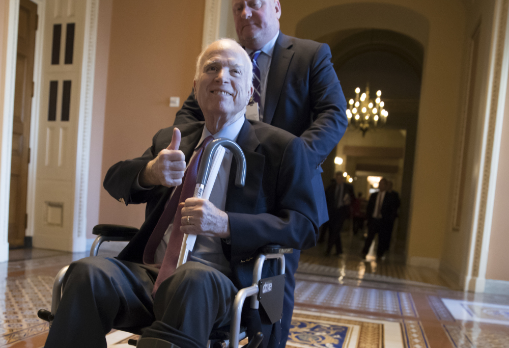 Sen. John McCain, R-Ariz., leaves a closed-door session where Republican senators met on the GOP effort to overhaul the tax code on Dec. 1. McCain is returning home to Arizona after being hospitalized over the side effects from his brain cancer treatment. The 81-year-old McCain has been hospitalized at Walter Reed Medical Center in Maryland.