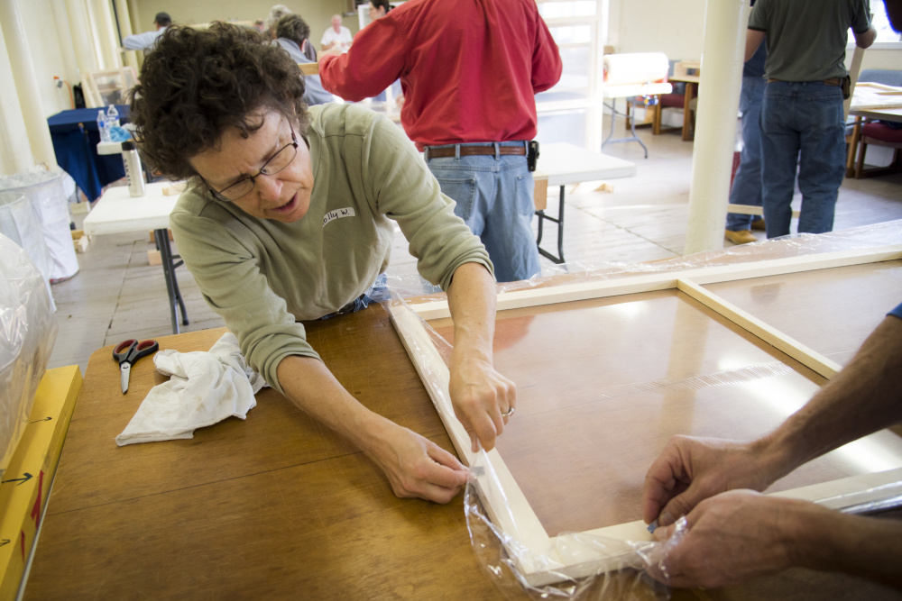 Holly Weidner of Vassalboro cuts excess plastic from a wooden frame as she helps prepare window inserts for residents who needed to insulate their windows. The Friends Advocating for Vassalboro's Older Residents committee gathered community volunteers together over the weekend to measure, build and distribute the plastic windows.