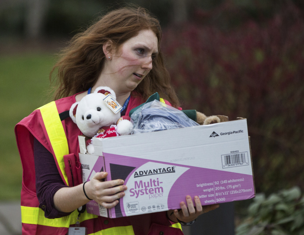 A volunteer carries out a box of supplies, including a teddy bear, from the DuPont, Wash., City Hall following a passenger train derailment in the area earlier Monday.