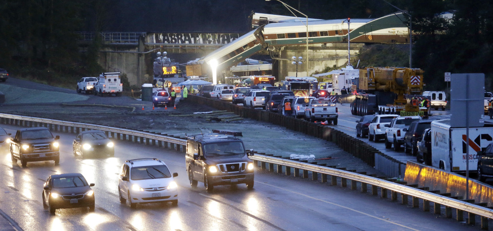 Traffic moves along northbound Interstate 5, left, as southbound lanes are filled with emergency vehicles near the scene of an Amtrak train crash Monday in DuPont, Wash.