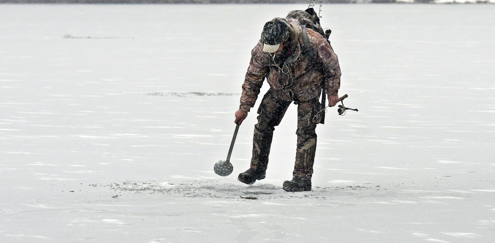 Eric Crowly of Monmouth strains ice in a hole Monday on Cochnewagon Lake in Monmouth. The angler caught one brook trout beneath 5 inches of ice along the shoreline.