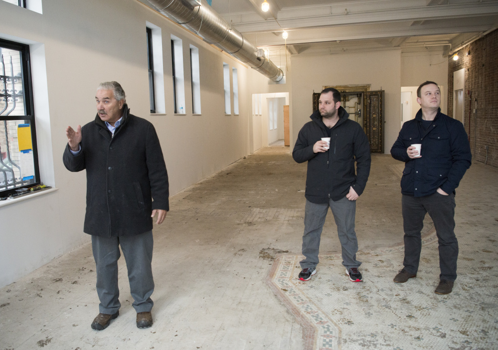 Paul Ureneck, left, director of commercial real estate for Elm City LLC, an affiliate of Colby College, describes how construction will evolve over the next few months at a gathering Tuesday at the Hains building on Main Street in downtown Waterville. Selah Tea owner Bobby Magee, center, and Colby's vice president for planning, Brian Clark, attended.