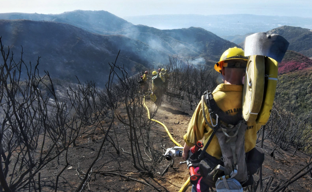 Mike Eliason/Santa Barbara County Fire Department via AP Firefighters work along steep terrain to root out and extinguish smoldering hot spots in Santa Barbara, Calif., on Tuesday.