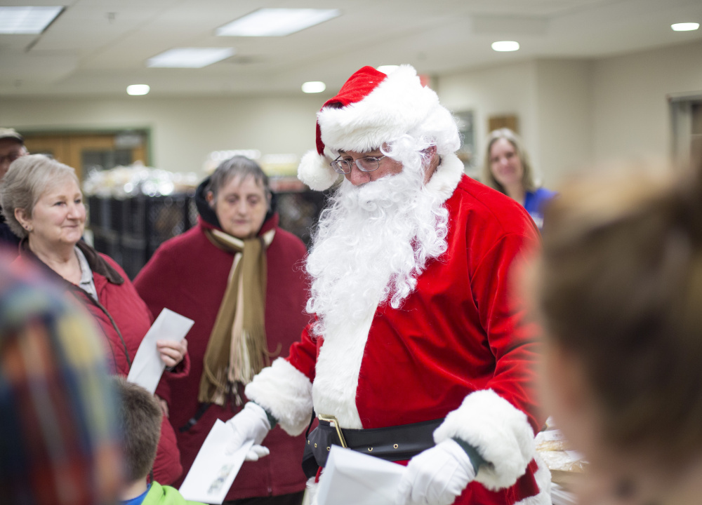 A Secret Santa passes out $100 bills at the Standish Food Pantry on Wednesday.